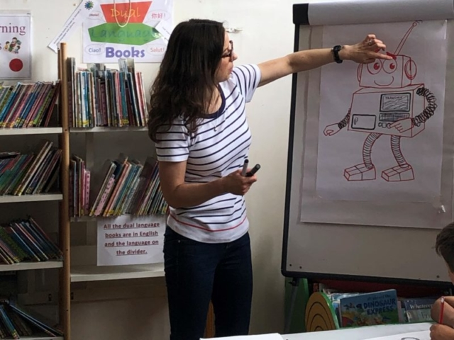 Emily teaching a library group to draw a space robot