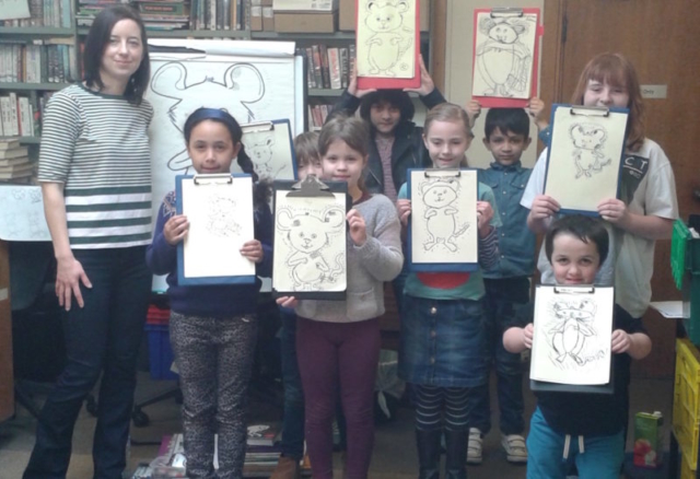 Children holding up their mouse drawings after and Arts Award workshop