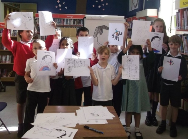 Children hold up their drawings after a superhero workshop