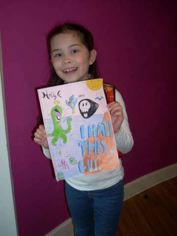 Girl holding up her picture book creation for the Arts Award