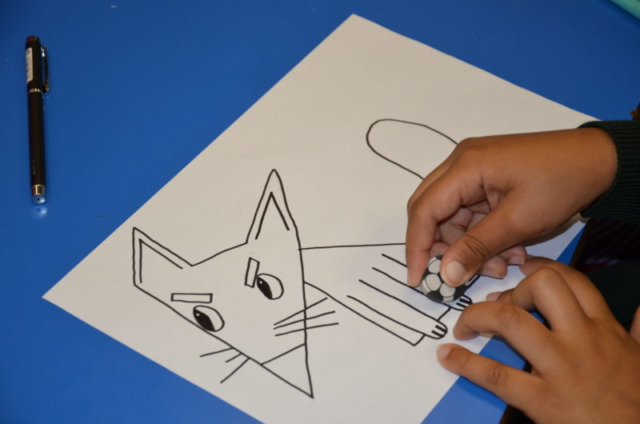 A pupil rubbing out pencil lines from an inked fox character following a step-by-step tutorial.