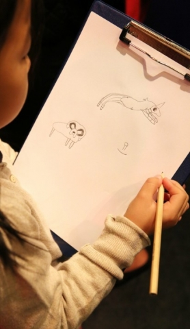 A young artist drawing during my workshop.