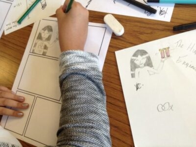 A child starting a comic strip having created original characters.