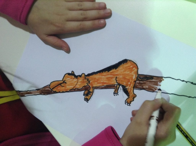 Child colouring her version of 'Lazy the Sabre-Toothed Tiger'