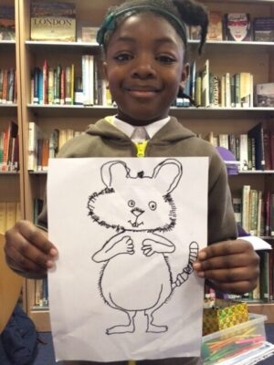 A girl holding up a drawing of a mouse she has done