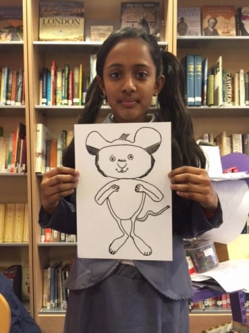 Girl holding up her Ishmael Mouse drawing