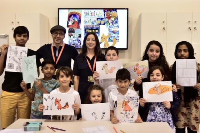 Children holding up their work after a comics workshop