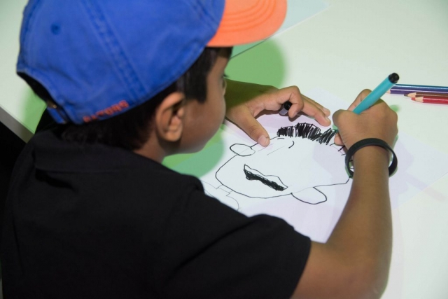 A child drawing 'Big Nate' from a step-by-step demo
