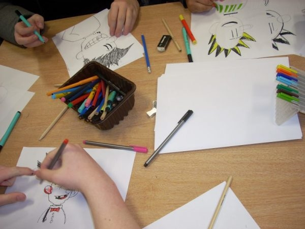 Children drawing comic characters during a workshop