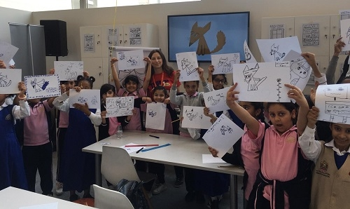 Emily Fellah with a school group holding up the drawings they've created in the workshop