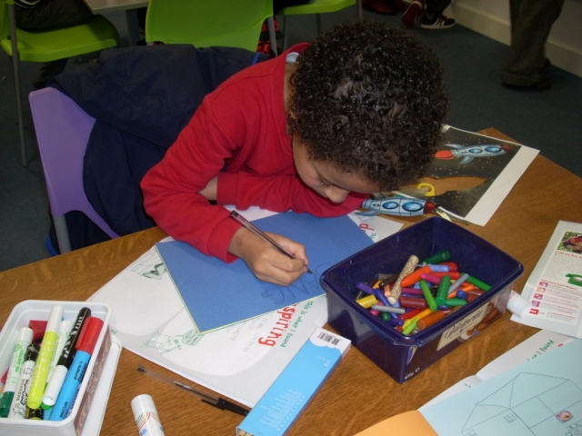 Boy creating a picture book with drawing and collage