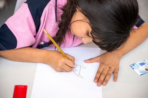 A girl drawing a fox based on triangles