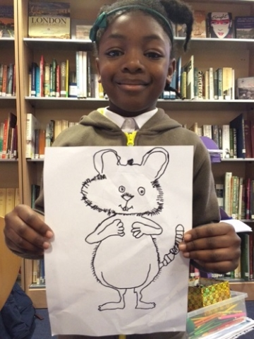 A girl holding up a drawing of a mouse